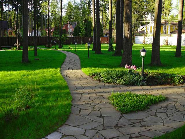По благоустроенной территории у частного дома приятно гулять.