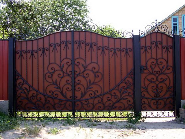 Сначала ставим ворота со створками из листового металла, а затем украшаем их ковкой.